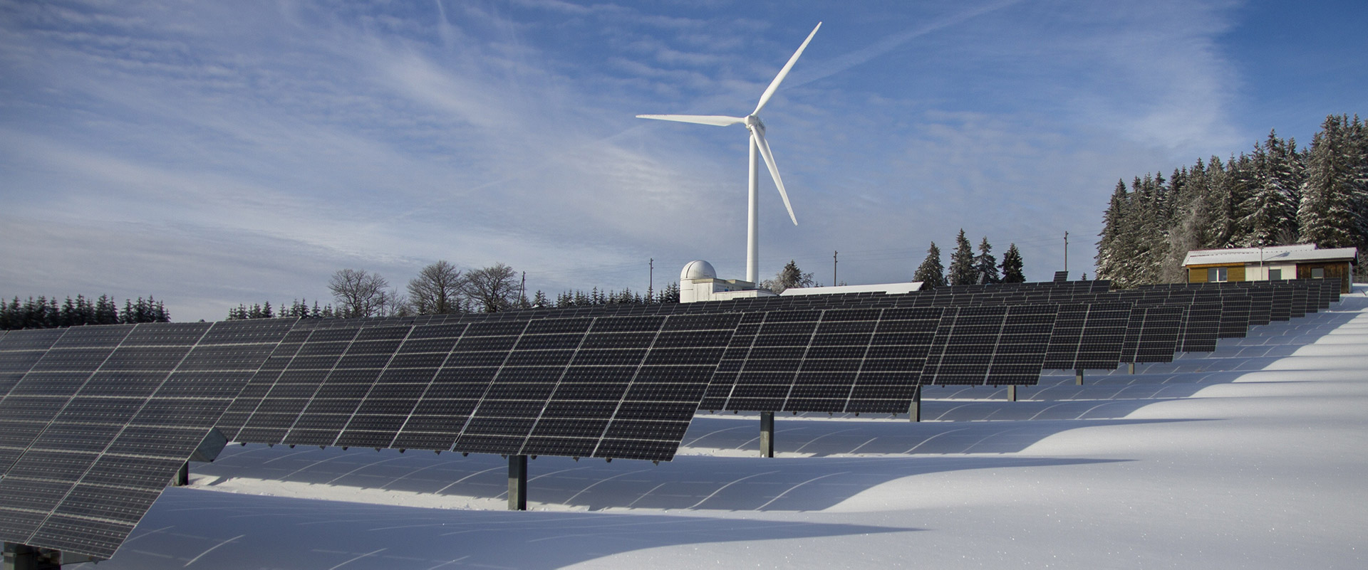 solar panels and wind turbine on a snowy field